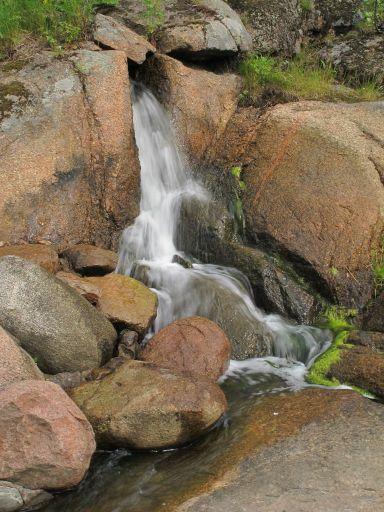 В стороне небольшой водопад